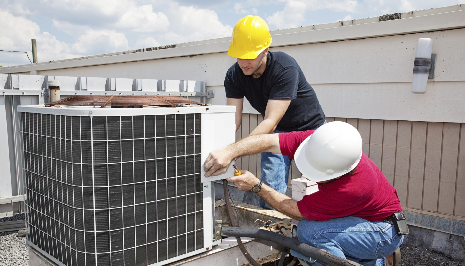 Workers Installing an Air Conditioner on a Roof